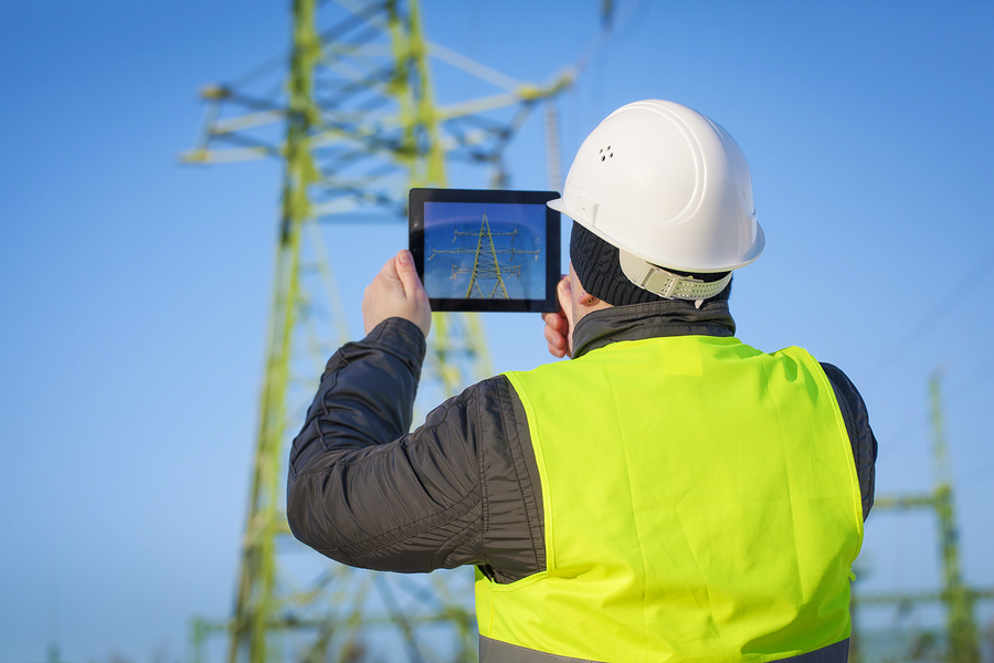 Man near AC power line with tablet